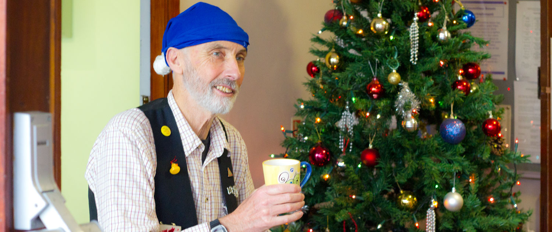 Volunteer greeting Christmas Fayre Visitors dressed as an Elf